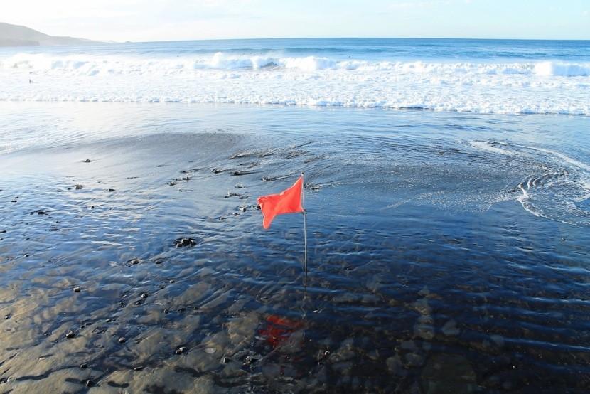 Červená vlajka na pláži